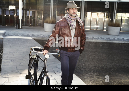 Mid adult man walking with bicycle in city - Stock-Bilder