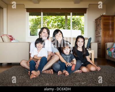 Portrait of family sitting in living room - Stock-Bilder