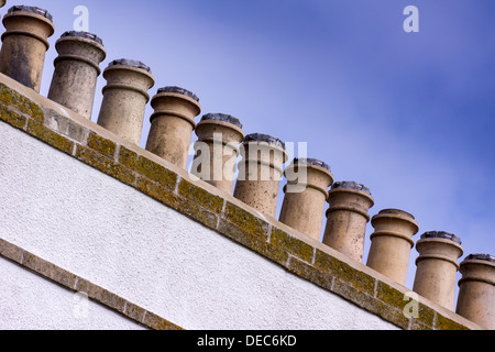 A line of eleven chimney pots on a whitewashed chimney stack stand out against a blue sky. - Stock Image