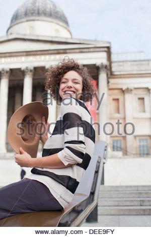 Exuberant woman with hat below historical landmark in London - Stock-Bilder