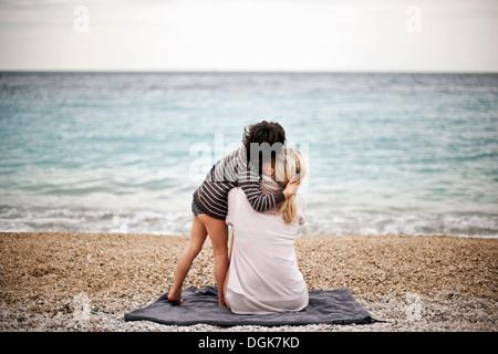 Boy hugging mother on a beach, rear view - Stock-Bilder