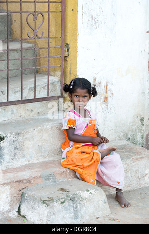 Indian lower caste infant girl sitting on a house step.  Andhra Pradesh, India - Stock Image