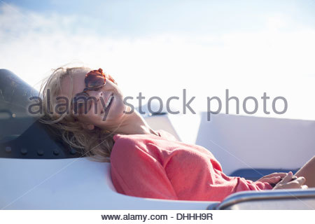 Woman wearing sunglasses laughing on yacht, Wales, UK - Stock Image
