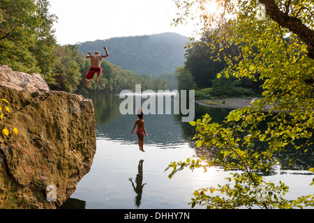 Young couple jumping from rock ledge, Hamburg, Pennsylvania, USA - Stock-Bilder