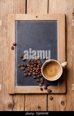 Coffee cup with coffee beans on vintage slate chalk board - Stock-Bilder