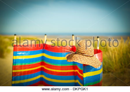 Straw hat on wind barrier on beach - Stock-Bilder