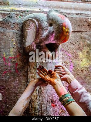 Henna Hands take Holi water from Ganesh Bankey Bihari Temple, Vrindavan during Holi - Stock-Bilder