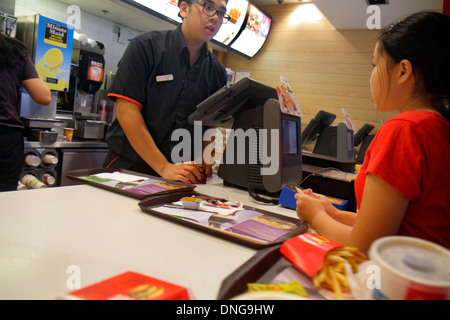 Hong Kong China Kowloon Sham Shui Po McDonald's fast food restaurant counter employee job Asian man girl customer - Stock Image