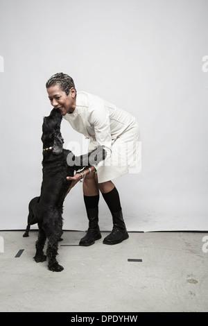 Studio shot of mature woman having fun with pet dogs - Stock-Bilder