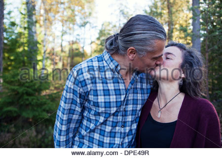 Mature couple kissing in woods, Mariefred, Sweden - Stock Image