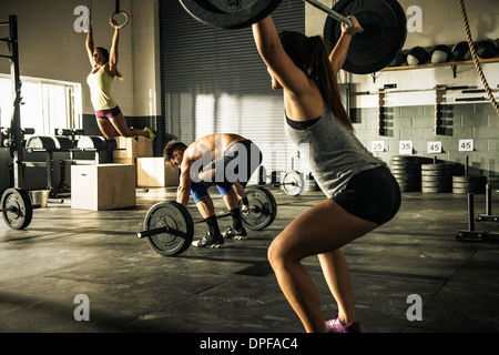 People training with barbells and gymnasium rings - Stock-Bilder