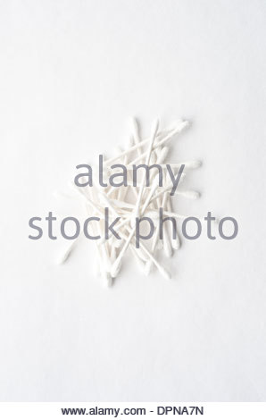 Pile of white q-tips in different directions shot from above on white background. - Stock Image
