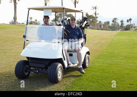 Portrait of two male golfers in golf buggy - Stock Image