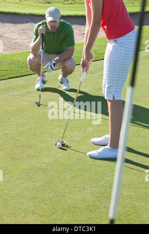 Young female lining up golf ball with trainer - Stock Image