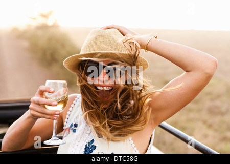 Young woman wearing hat holding glass of wine - Stock Image