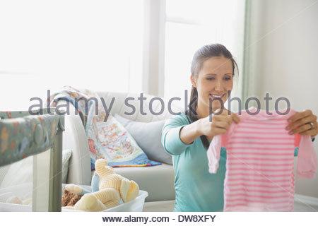 Pregnant woman holding baby onesie in nursery - Stock-Bilder