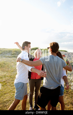Cheerful friends enjoying at beach - Stock Image