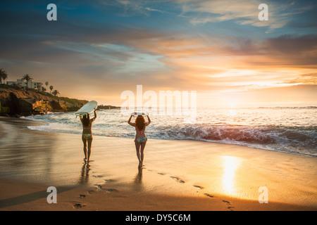 Surfers carrying surf board, walking along beach - Stock Image