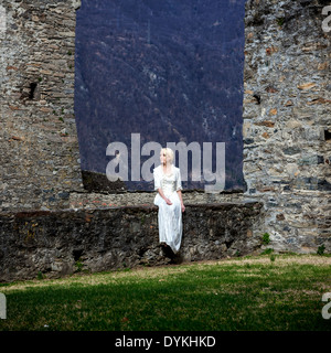 a woman in a white period dress is sitting on a wall at a castle - Stock Image