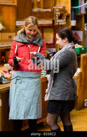 LONDON, UK A customer tries a cheese sample at London's Borough Market. - Stock Image