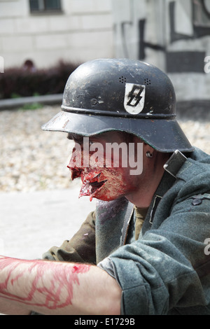 Male participant in the Prague zombie walk may 2014 photographed in profile wearing a soldiers uniform and a soldiers - Stock Image