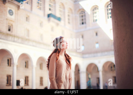 Young woman gazing up in historic courtyard - Stock Image