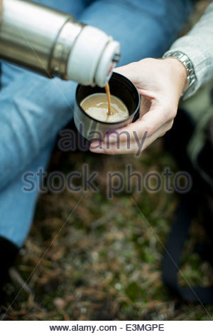 Cropped image of man pouring cup of coffee outdoors - Stock Image