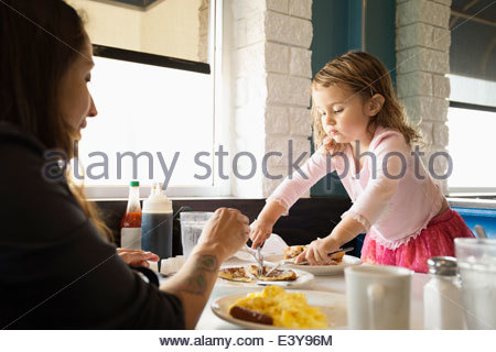 Mother and toddler daughter eating in diner - Stock-Bilder