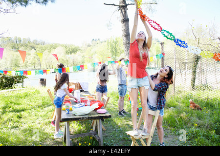 Young woman hanging up bunting - Stock-Bilder