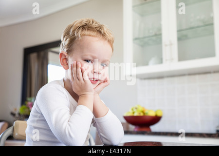 Portrait of cheeky four year old boy in kitchen - Stock Image
