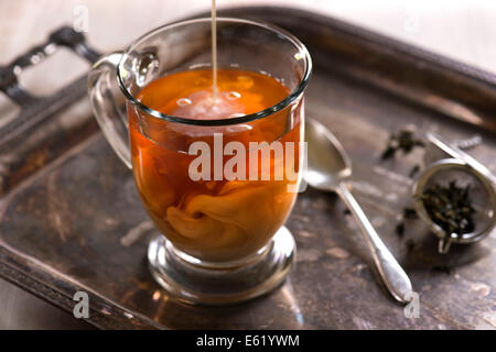 A glass of tea with milk pouring in and swirling. Antique, rustic styling with light background. - Stock Image