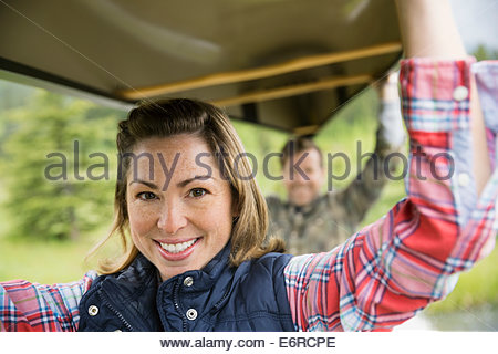 Couple carrying canoe outdoors - Stock Image