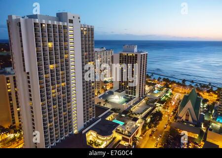 Hawaii Hawaiian Honolulu Waikiki Beach Pacific Ocean high rise buildings hotels condominium dusk night city skyline - Stock Image