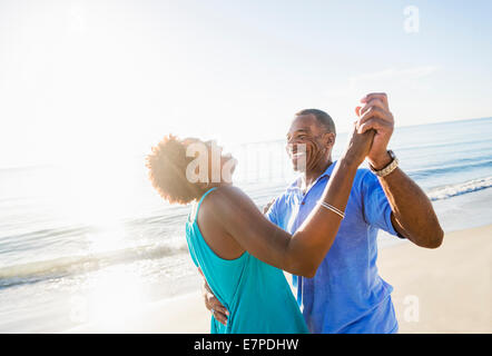 Mature couple dancing on beach - Stock-Bilder