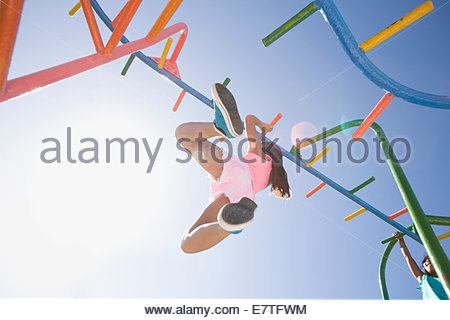 Girl hanging from monkey bars at playground - Stock Image