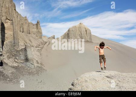 Boy jumping on sand dunes - Stock-Bilder