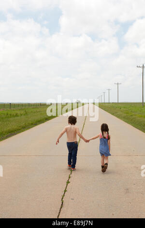 Brother and sister walking along sidewalk in country - Stock-Bilder