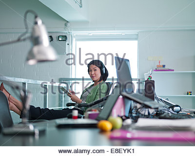 Businesswoman with headphones writing on note pad in office - Stock-Bilder