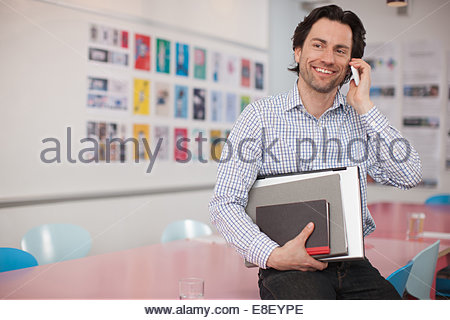 Smiling businessman holding laptop and books talking with cell phone  in office - Stock-Bilder