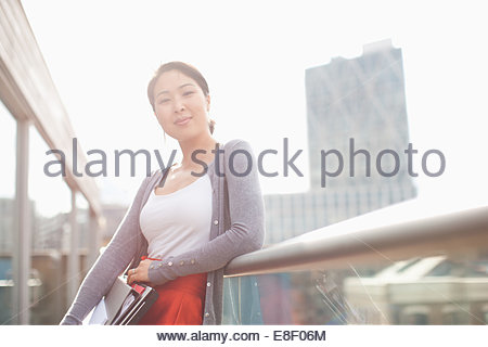 Smiling businesswoman holding folders and leaning on railing of urban balcony - Stock-Bilder