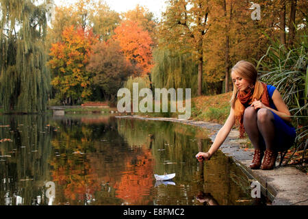 Young woman with paper ship in park - Stock-Bilder