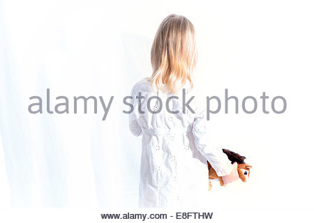 Rear view of a Girl holding a soft toy - Stock Image
