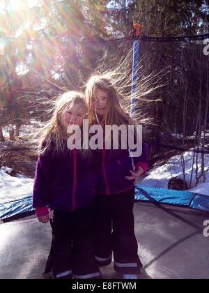 Sweden, Two girls (6-7 years, 8-9 years) on trampoline with static hair - Stock Image
