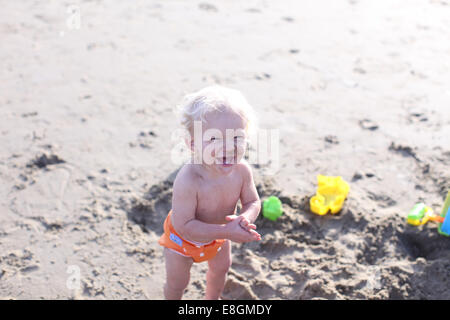 Toddler laughing on beach - Stock Image