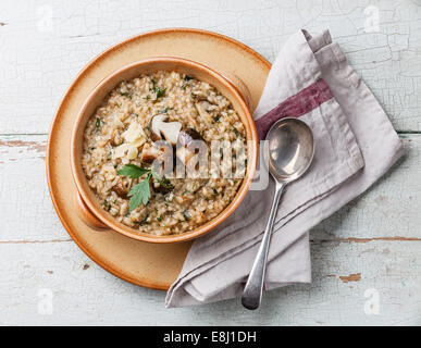 Risotto with wild mushrooms with parsley and parmesan on blue background - Stock-Bilder
