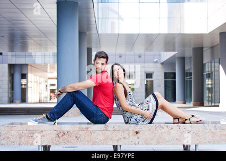 Happy young couple sits back to back on campus - Stock-Bilder