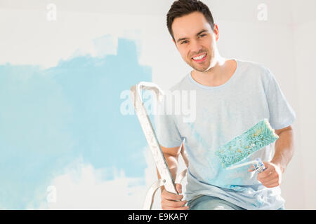 Portrait of happy man painting his new house - Stock-Bilder