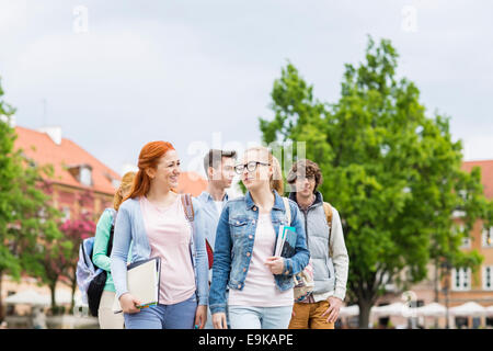 Group of college friends walking outdoors - Stock Image
