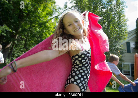 Girl in swimming costume holding towel - Stock Image
