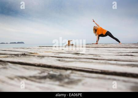 Mid adult woman practicing yoga position on wooden sea pier - Stock-Bilder